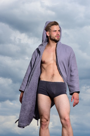 Adult handsome man in fashionable bathrobe. Morning concept. Sexy young macho on the sky. Male model posing against the sky. Bearded attractive guy enjoy healthy morning. Stock Photo