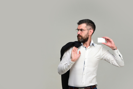 barbershop: Guy with blank business card, copy space. Man with beard holds white card. Success and business introduction concept. Businessman with serious face and glasses isolated on grey background
