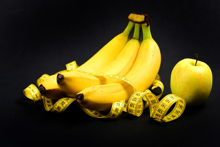 Tape for measuring wrapped around bananas near green apple on black background. Concept of eco food lifestyle Stock Photo