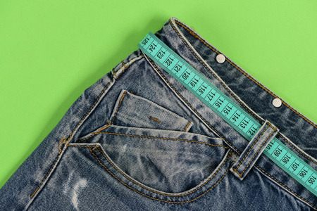Healthy lifestyle and dieting concept. Jeans with blue measure tape instead of belt. Close up of jeans belt loops and pocket. Top part of denim trousers isolated on green background.