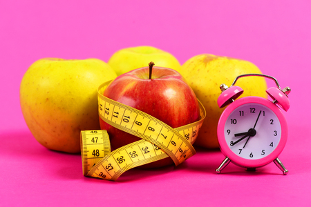 Tape for measuring in yellow color wrapped around red apple near yellow apples and alarm clock, isolated on magenta pink background