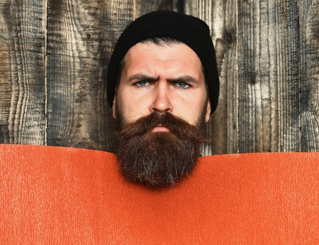 barbershop: Bearded man, long beard. Brutal caucasian serious unshaven hipster in black hat with red paper sheet on grey wooden vintage studio background, copy space Stock Photo