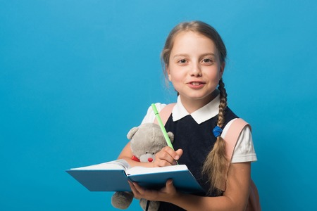 Girl with braids and happy face. Kid in school uniform isolated on blue background with copy space. Pupil writes in blue book with green marker and holds teddy bear. Study and back to school concept.