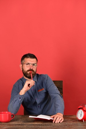 Cup, retro clock and red book on vintage table. Exam and studying concept. Teacher with thinking face sits at wooden table. Man with beard and glasses holds notebook and marker on red background