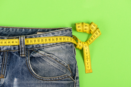 Close up of jeans with measure tape around waist. Healthy lifestyle and dieting concept. Upper part of denim trousers isolated on green background. Blue jeans with yellow measure tape instead of belt.