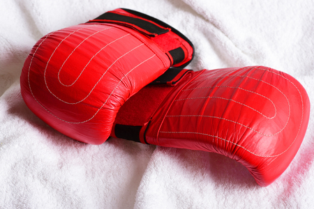 Pair of red boxing gloves lying on white towel background. Concept of boxing sport and gym