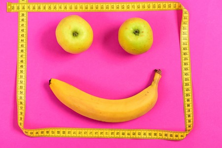 smiley pouce: Apples and banana with yellow measuring tape make happy smiling face, isolated on pink background Banque d'images