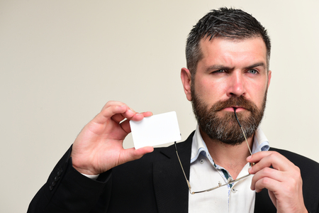 barbershop: Guy with thoughtful face and glasses isolated on light grey background. Business and success concept. Businessman with empty card, copy space. Man in suit with beard holds white business card