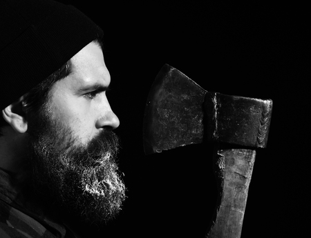 Handsome man or lumberjack, bearded hipster with white beard and moustache in hat looks at old rusty iron blade of axe isolated on black background