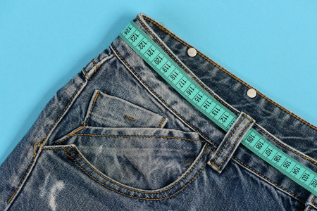 Healthy lifestyle and dieting concept. Top part of denim trousers isolated on blue background. Jeans belt loops and pocket in close up. Jeans with blue measure tape instead of belt.