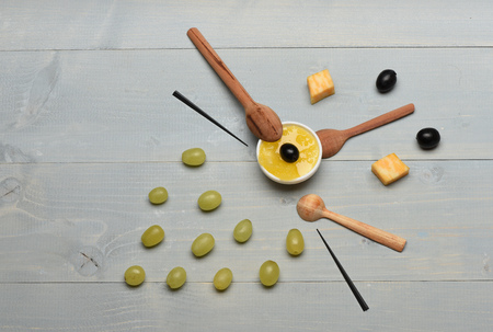 toothpick: Face made of food and skewers. Wooden spoons and honey, top view. Composition of cheese and grapes on vintage background. Art and healthy food concept.