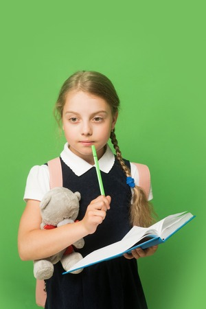 blue green background: Kid in school uniform isolated on green background. Study and back to school concept. Girl with braids and thoughtful face expression. Pupil holds blue book, marker and teddy bear.