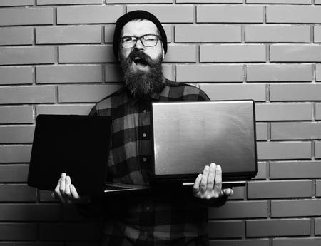 barbershop: Bearded man, long beard. Brutal caucasian unshaven hipster holding laptops in red black checkered shirt with hat and glasses on brown brick wall studio background