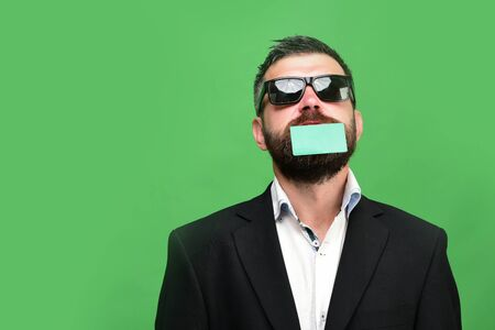 Business and success concept. Man in classic suit holds green business card on beard. Guy with funny face and sunglasses isolated on green background. Businessman with empty card, copy space