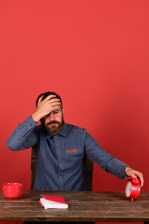 Man with beard and glasses holds alarm clock, red background. Cup, retro clock and red book on vintage table. Exam and studying concept. Professor with worried face sits at wooden table Stock Photo