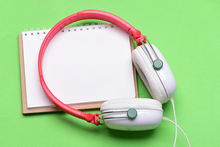 Headset for music and blank page with copy space. Music accessories concept. Modern and stylish earphones isolated on light green background. Headphones in white and red color with empty notebook