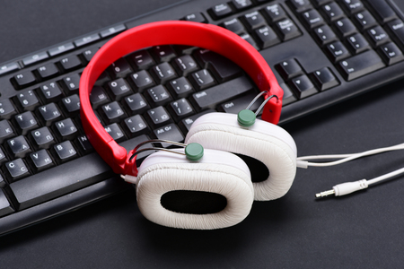 Electronic appliances on black background. Sound recording and technology idea. Headphones and keyboard. Earphones in red and white colors with computer keyboard. Music and digital equipment concept Stock Photo