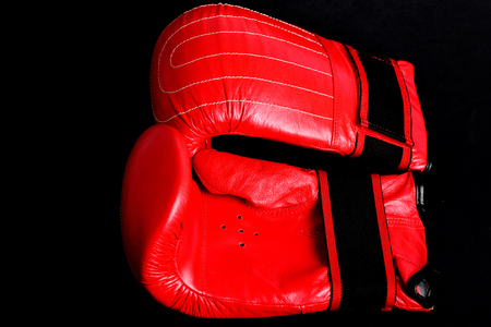 Red boxing gloves for heavyweight sport isolated on black blank background. Concept of professional gym and training Stock Photo