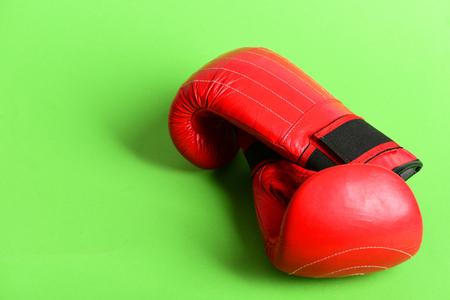 Equipamento de esporte isolado no fundo verde. Caixa profissional e conceito de luta forte. Luvas de boxe na cor vermelha. Par de sportswear de boxe de couro Foto de archivo - 83749888