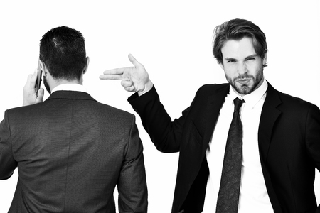 sabotage: diversion and sabotage, harassment, corruption, man with gun gesture shooting busy businessman speaking on phone in formal suit isolated on white background Stock Photo