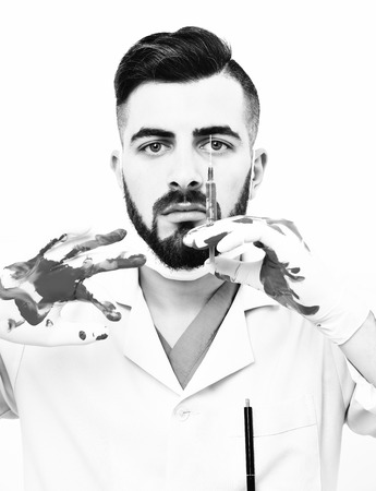 barbershop: Doctor with serious face expression and dark beard holds syringe in bloody hand, isolated on white background. Concept of medicine and ambulance services Stock Photo