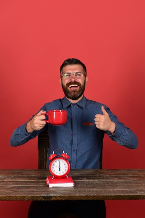 barbershop: Exam and studying concept. Retro clock and red book on vintage table. Teacher with happy face sits at wooden table and shows thumbs up. Man with beard and glasses holds tea mug, red background