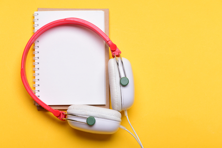 Headset for music and blank page with copy space. Headphones in white and red color with empty notebook. Music and note taking concept. Modern earphones isolated on yellow background, top view