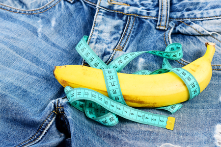 Mens denim pants crotch with banana imitating male genitals. Health and male sexuality concept.  Jeans zipper and pocket, close up. Banana wrapped with blue measure tape on jeans, selective focus.