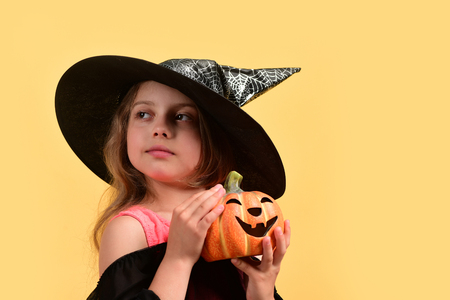 Kid in black witch hat, dress and tricky face. Child in witch costume and jack o lantern. Halloween and autumn holiday concept. Girl with carved orange pumpkin isolated on warm yellow background Stock Photo