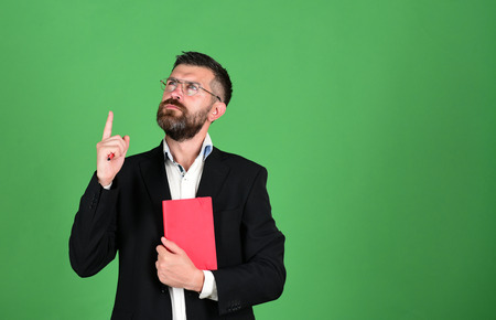 hairdresser: Teacher wears glasses and holds organizer. Man with beard and book. Notebook in red color in guys hands on green background, copy space. Professor has new idea. Knowledge and scheduling concept