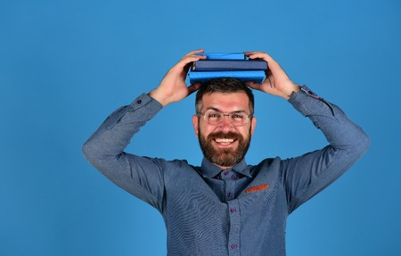 Man with happy face, glasses and beard holds books on head, blue background