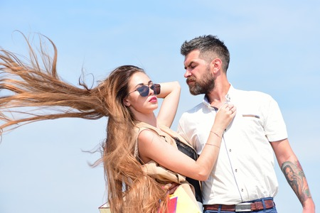 hairdresser: Couple holds packets on blue background. Sexy girl and guy with serious face expressions hug each other. Relationship and love concept. Man with beard and woman with messy long hair waving on wind