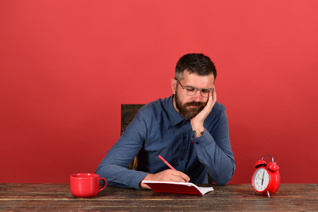 barbershop: Cup, retro clock and red book on vintage table. Professor with bored face sits at wooden table. Exam and studying concept. Man with beard and glasses writes in notebook on red background