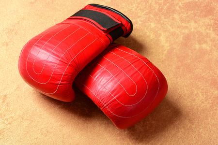 Equipo deportivo sobre fondo de papel naranja. Guantes de boxeo en color rojo. Caja profesional y concepto de pelea fuerte. Par de ropa deportiva de boxeo de cuero Foto de archivo - 83883789