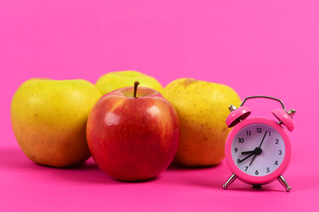 Apple fruit set of red and yellow colors and pink retro alarm clock isolated on magenta pink background. Concept of vintage style and morning food regime Stock Photo