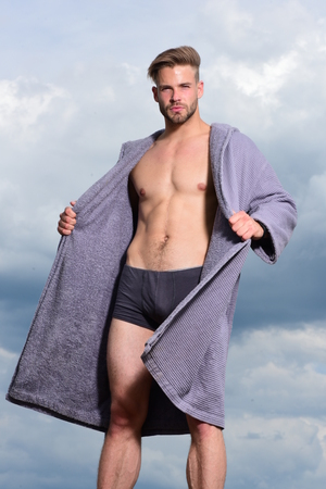 Sexy young macho on the sky. Male model posing against the sky. Morning concept. Adult handsome man in fashionable bathrobe. Bearded attractive guy enjoy healthy morning. Stock Photo