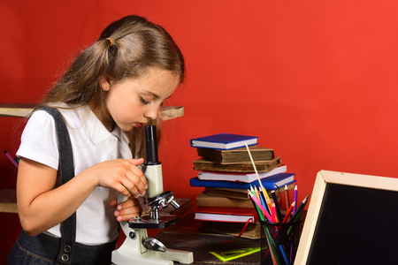 Kid with school and lab supplies on red wall background. Girl looks into microscope, copy space. Schoolgirl with concentrated face does experiment in her classroom. Back to school and science concept