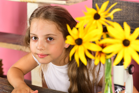 Kid and school supplies on pink wall background. Girl with smiling face in her room. Schoolgirl at her desk with yellow flowers, defocused. Back to school and natural beauty concept