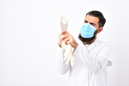 Medical worker with blue medical mask. Medical worker putting on white gloves isolated on white background, copy space. Physician with beard in white gown. Medicine and health concept