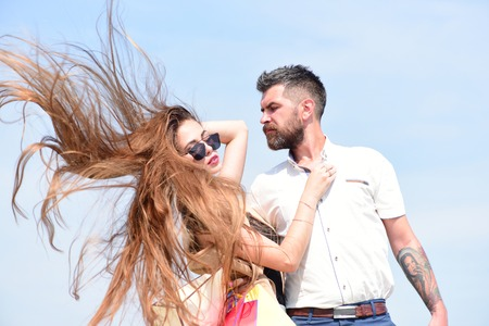 barbershop: Sexy girl and guy with tender face expressions hug each other. Shopping and love concept. Man with beard and woman with messy long hair hold shopping bags. Couple carries packets on blue background