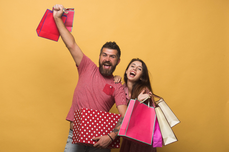 hairdresser: Bearded man and young girl with happy faces. Couple holding shopping bags high on yellow background. Guy with beard and pretty lady do shopping, having fun. Shopping and relationship concept