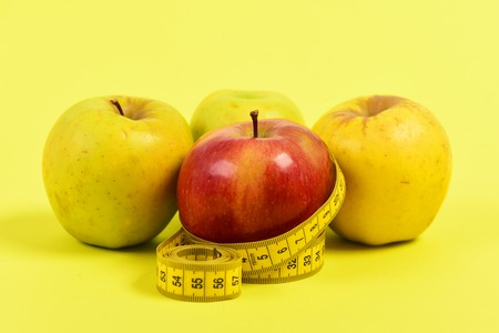 Tape for measuring and four apples, isolated on yellow background. Concept of diet and healthy food Stock Photo