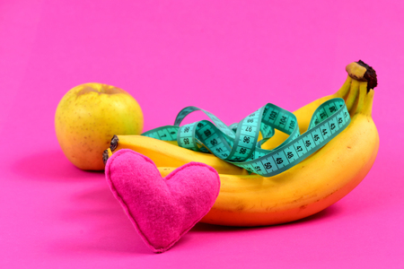 Composition of bananas, apple, greenish blue measuring tape and pink heart, isolated on rosy background