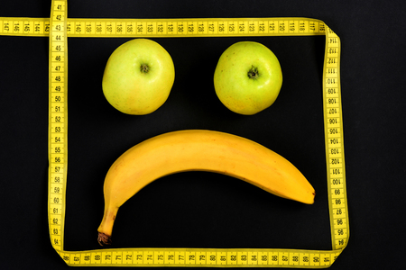 smiley pouce: Scared smiley face with ripe banana and green apples framed with square of yellow measuring tape isolated on black background, top view. Concept of vegetarian nutrition, emotions and food art