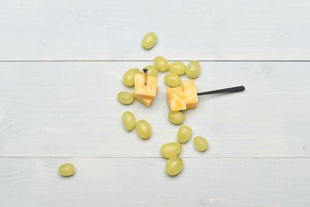 Composición de brochetas de queso de mármol y uvas. Varias uvas blancas sobre fondo vintage. Concepto de comida gourmet Delicioso aperitivo con queso y fruta de verano, vista superior.