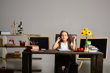 hairdresser: Back to school and childhood concept. Girl sits at her desk with books, fruit and colorful stationery. Schoolgirl with grumpy face draws in art book. Kid and school supplies on grey wall background.