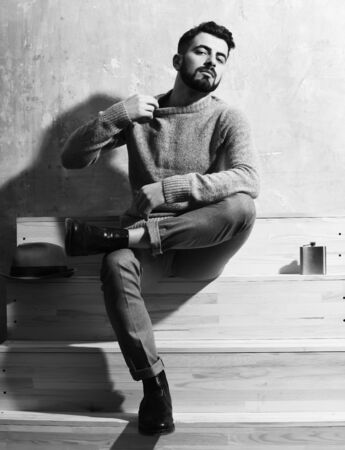 hairdresser: bearded man, long beard, brutal caucasian hipster with moustache in sweater sitting on wooden stairs with hat and flask with serious face on studio wall background Stock Photo