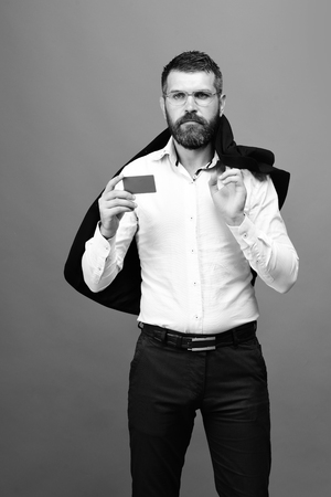 hairdresser: Man with beard in white shirt and suit holds blue business card. Businessman with empty card. Business and people at work concept. Guy with serious face and glasses isolated on blue background