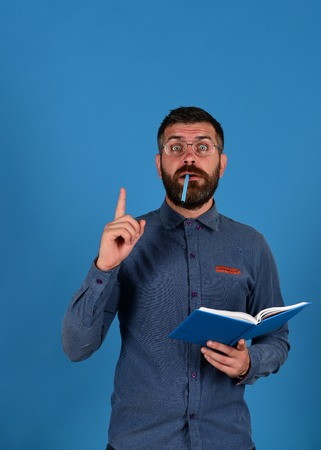 hairdresser: Knowledge and scheduling concept. Notebook in blue color in guys hands isolated on blue background. Professor has new idea. Teacher wears glasses and holds organizer. Man with beard, book and marker Stock Photo