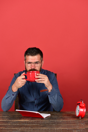 Man with beard and glasses holds mug and sits near notebook, red background. Exam and studying concept. Cup, retro clock, red book on vintage table. Teacher with thoughtful face sits at wooden table Stock Photo
